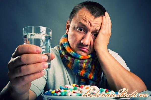 Мужчина с болью в голове со стаканом воды и таблетками