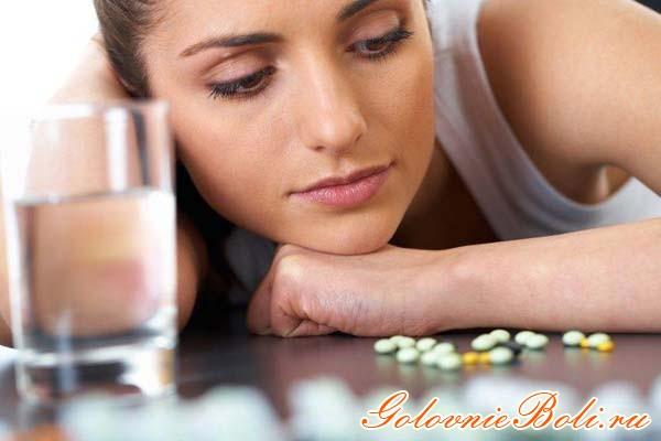 Девушка сидит за столом, на котором лежат таблетки