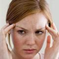 Девушка давит пальцами на виски, чтобы не болела голова