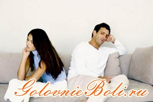 Мужчина и женщина сидят на диване, отвернувшись друг от друга
