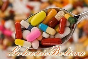 Различные таблетки и капсулы в ложке