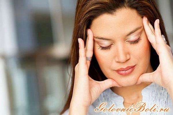 Девушка держится за голову руками, потому что болит голова