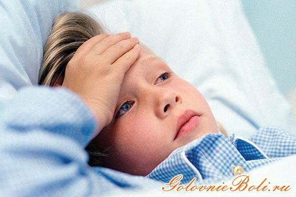 Ребенок лежит в кровати и держится рукой за лоб, у него болит голова